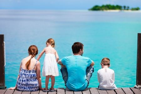 Family on wooden dock looking to ocean and tropical fishes photo