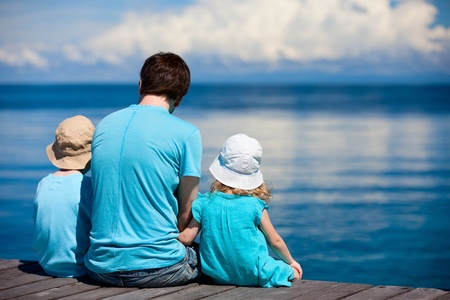 Back view of father and kids sitting on wooden dock looking to ocean Stock Photo