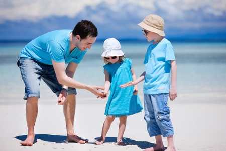 Father and kids at tropical beach holding starfish photo
