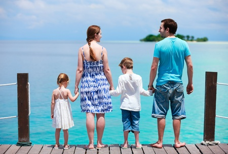Family on wooden dock enjoying ocean view photo
