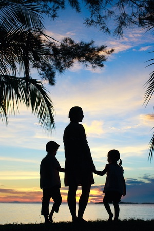 Silhouettes of mother and two kids at sunset photo