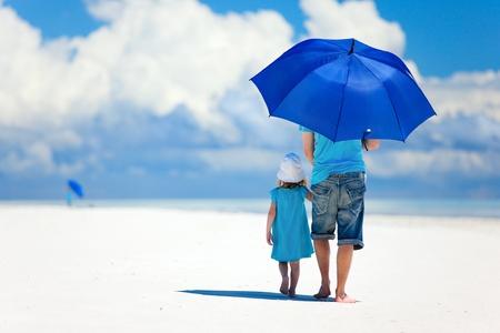 Ojciec i córka na plaży z parasolem, aby ukryć przed słońcem