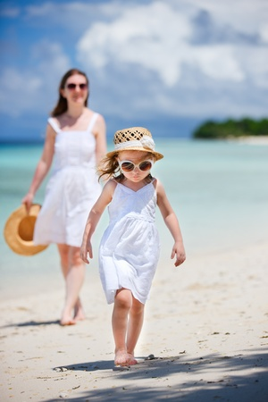 Adorable little girl and her mother walking along tropical beach photo