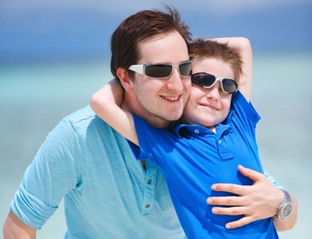 sunglasses beach: Portrait of happy father and son on summer vacation Stock Photo