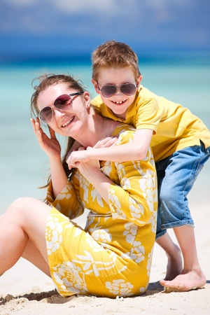 Happy beautiful mother and son enjoying beach time photo