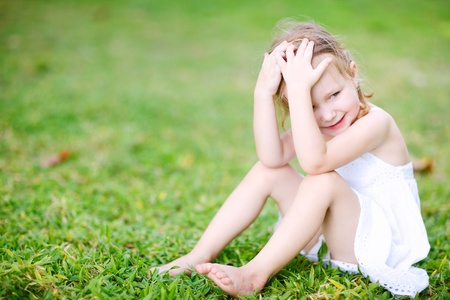 Adorable little girl sitting on a grass photo