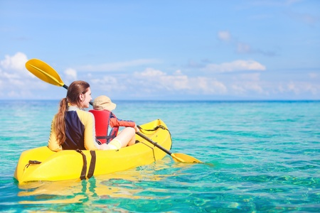 Mother and son kayaking at tropical ocean photo