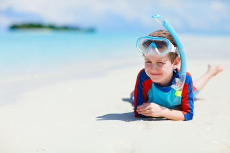 Cute boy with snorkeling equipment at tropical beach photo