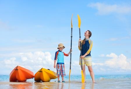 kayak: Gelukkige moeder en zoon op het strand na kajakken