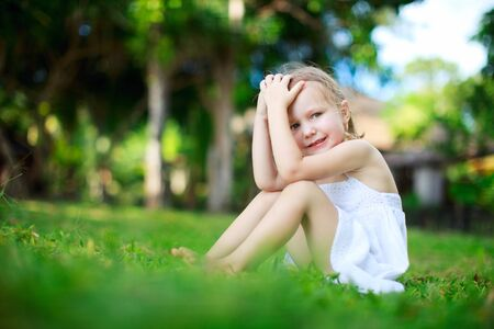 beauty girl pretty: Adorable little girl sitting on a grass