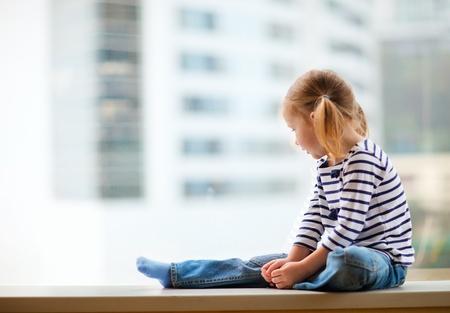 rozkošný: Rozkošná holčička sedí u okna