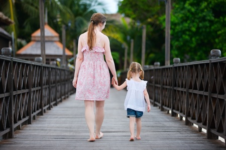 little girl barefoot: Back view of mother and daughter walking along wooden jetty Stock Photo
