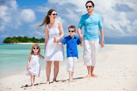 turquoise: Young beautiful family with two kids walking at beach