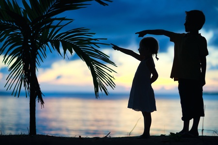 Silhouettes of two little kids at sunset photo