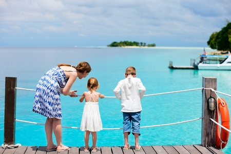 Mother and kids on wooden dock enjoying ocean view photo