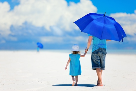 sun umbrellas: Father and daughter at beach with umbrella to hide from sun