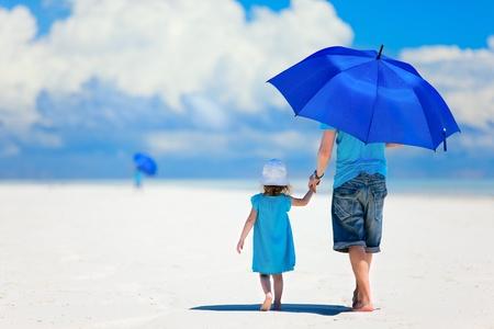 Vader en dochter op het strand met een paraplu te verbergen tegen de zon Stockfoto