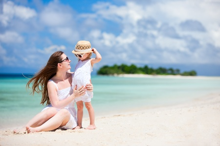 Young beautiful mother and her adorable little daughter at tropical beach photo
