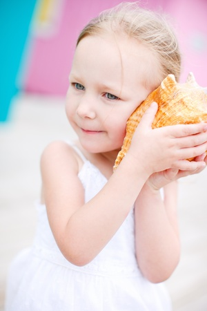 Adorable little girl with conch shell  Colorful Caribbean house on background photo