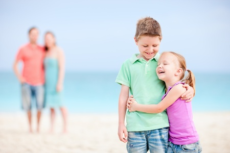 Brother and sister embracing each other while parents standing on background photo