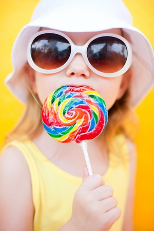 Adorable little girl with lollipop over colorful background photo