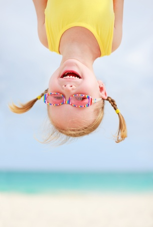 Adorable little girl hanging upside down having fun photo