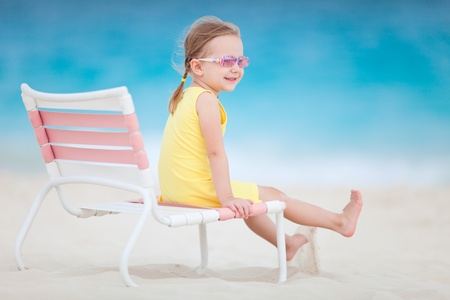 Portrait of sweet little girl sitting on chair at tropical beach photo