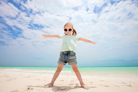 little girl child: Portrait of cute little girl at tropical beach made with wide angle lens