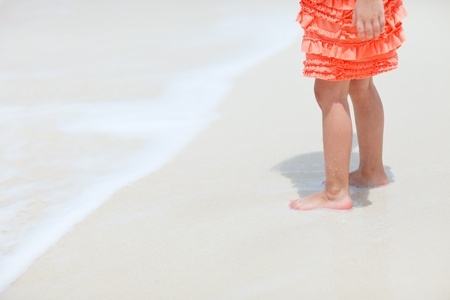 Little girl at tropical beach close up on legs photo