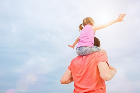 Back view of father carrying his little daughter on shoulders photo