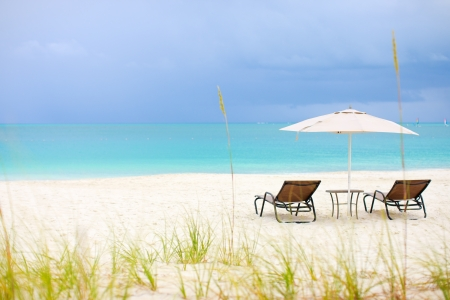 the turks: Two chairs under umbrella on stunning tropical beach in Turks and Caicos