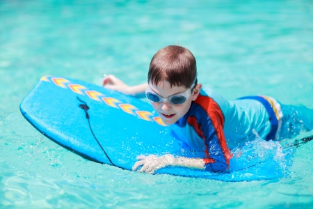 Little boy with surf board learning surfing photo