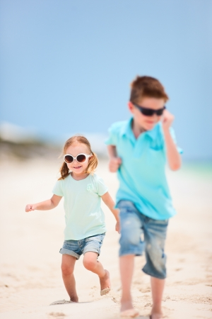 Small kids running at tropical beach photo