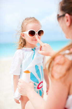 Mother applying sunblock cream on her daughters nose photo