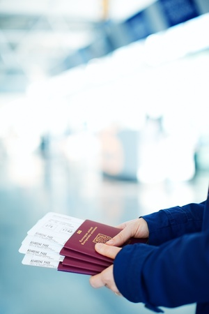 Close up of woman holding passports and boarding passport at airport photo