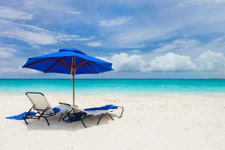 Two chairs under umbrella on beautiful tropical beach in Turks and Caicos photo