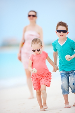 Mother and two kids running on tropical beach photo
