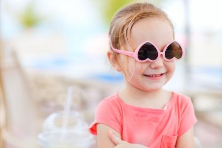 sole occhiali: Ritratto di bambina carina con gli occhiali da sole a testa in gi�