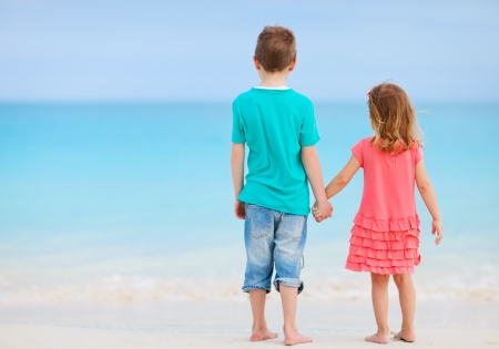 turks: Vista posterior de hermano y hermana en la playa tropical