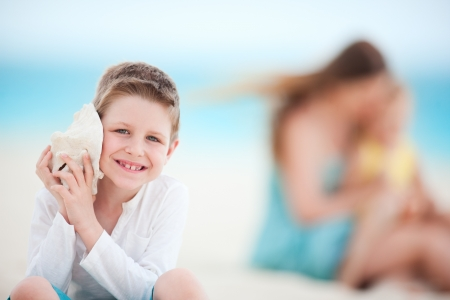 Cute boy with seashell at the beach with his family on background photo