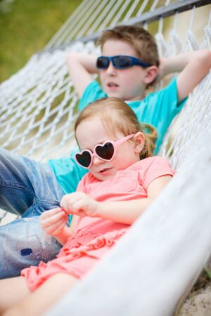 Brother and sister sitting in hammock photo