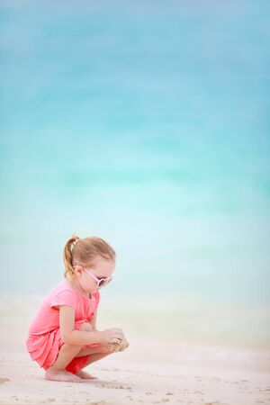 Adorable little girl playing with sand at tropical beach photo