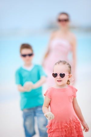 Adorable little girl and her family at tropical beach photo