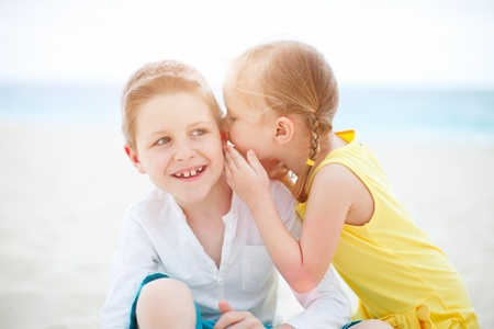 Adorable little girl telling secret to her brother photo