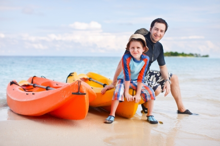 boating: Happy father and son after kayaking relaxing near boats Stock Photo