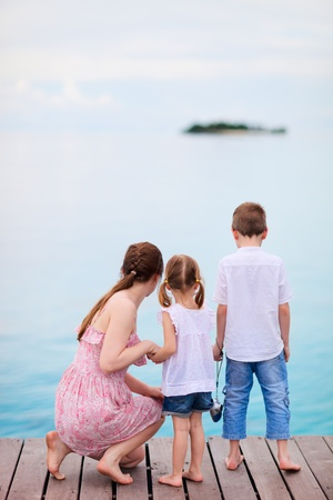 Mother and two kids at wooden dock enjoying ocean view photo