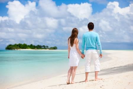 luna de miel: Vista trasera de la joven pareja en la playa tropical Foto de archivo