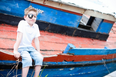 Outdoor portrait of cute pirate boy sitting at old boat photo