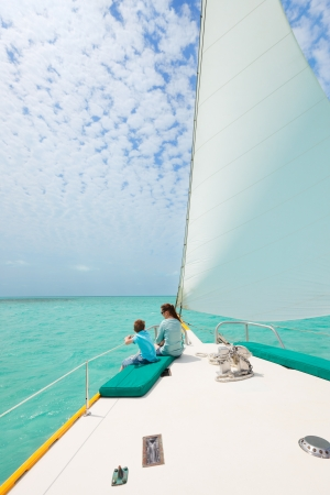 Mother and son relaxing while sailing on luxury yacht photo