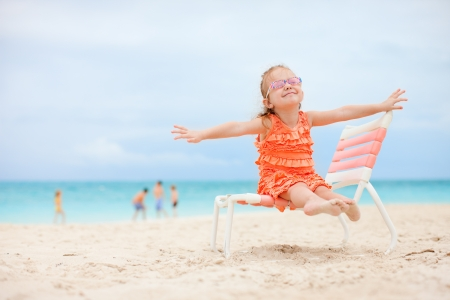 Happy little girl sitting on chair at tropical beach photo